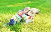 Šťastné dítě vytěžený Labradorský retrívr pes na trávě v létě