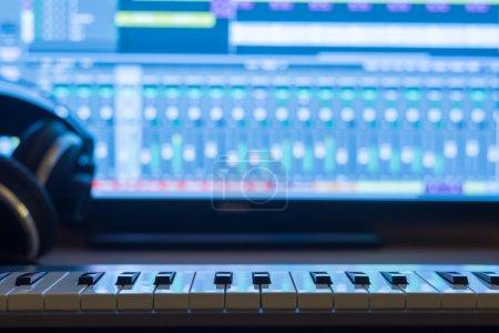 Photo pour Production musicale la nuit. Avec clavier et écouteurs . - image libre de droit