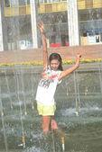 Veselá dívka tančí pod proudy vody v městské kašny