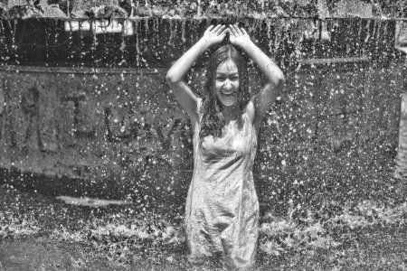 Girl in a slinky dress with long hair in water droplets in the city fountain
