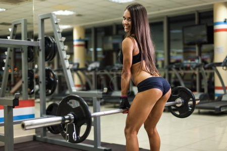 Photo for Bodybuilder girl with barbell in gym - Royalty Free Image