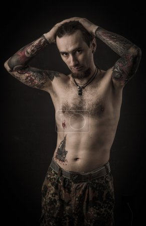Portrait of a man with naked torso and tattooes