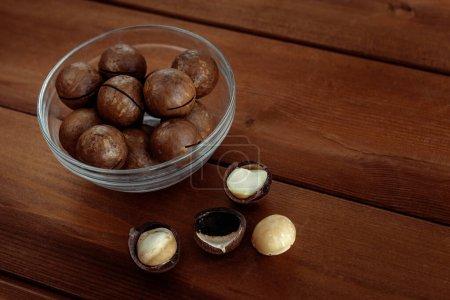 Photo pour Macadamia avec noix de noyau et noix dans un bol sur une table en bois. Aliments sains et collations - image libre de droit