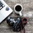 Laptop with digital camera and a coffee cup on old...