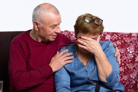 Photo pour Les conjoints âgés sont assis sur le canapé à la maison, la femme pleure, le mari l'embrasse et la réconforte. Triste événement de vie. Photo de haute qualité - image libre de droit