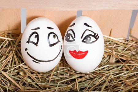 Photo pour Deux œufs dans un plateau de foin avec des visages peints d'amoureux hommes et femmes - image libre de droit