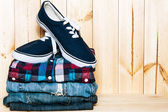 Still life with  blue sneakers, shirt and jeans on wooden  background, casual man