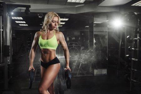 Foto de Deporte profesional mujer fitness con disco de peso en el gimnasio - Imagen libre de derechos