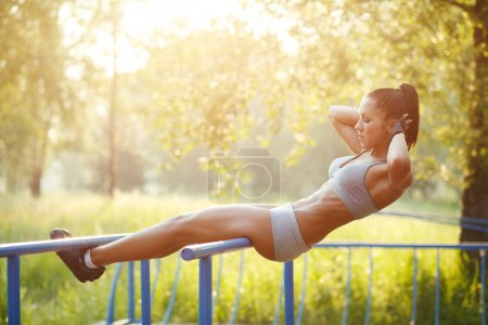 Beautiful fitness woman doing exercise on parallel bars outdoor. Sporty girl doing sit-ups on bars outdoors