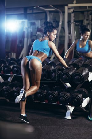 Photo for Sexy young brunette woman resting in the gym and leaning on row of dumbbells in a blue sport wear - Royalty Free Image