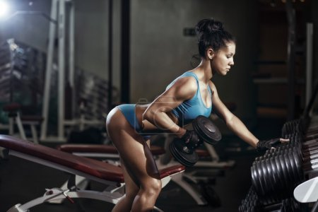 Brunette fitness girl lifting dumbbell. Fitness woman performing back exercises with dumbbells