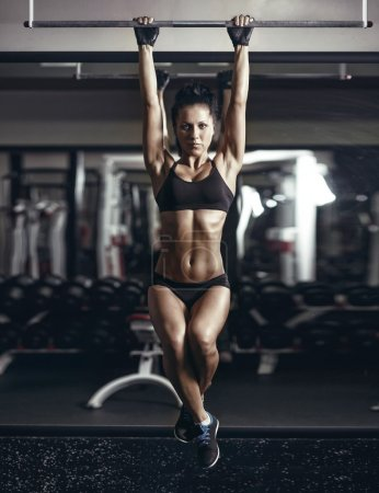 Sexy young fitness girl pulls up in the gym. Brunette fitness woman in black sport wear with perfect fitness body in gym performing abdominal exercises on the horizontal bar