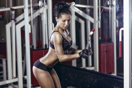Fitness woman doing triceps exercises in the gym. Brunette fitness girl in black sport wear with perfect body in gym exercising