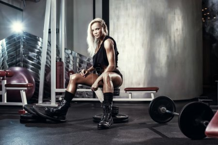 Photo for Fitness blonde sexy girl posing on bench in the gym in military style clothes - Royalty Free Image