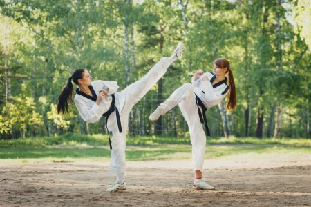 Two karate woman fighting on outdoor