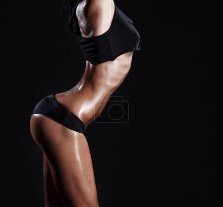 Sexy young muscled fitness brunette girl posing over black background. Fitness woman in sport wear with perfect fitness body