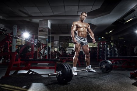 Very power athletic guy standing with barbell, workout in sport
