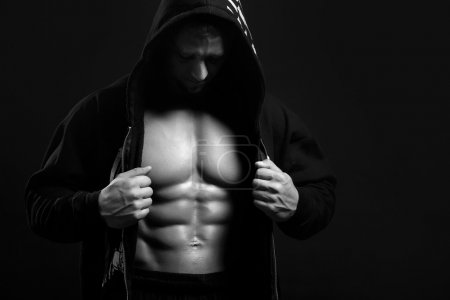Photo for Black and white strong man in the hood showing his press on blac - Royalty Free Image