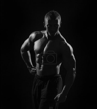 Muscular torso man with dumbbell on black background in studio. Bodybuilder working out biceps with dumbbell low key