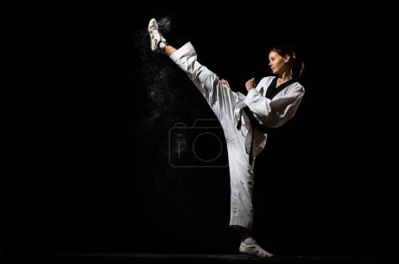 Young woman giving a kick on black background