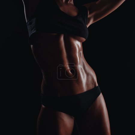 Photo for Sexy young muscled fitness brunette girl back posing over black background. Fitness woman in sport wear with perfect fitness body - Royalty Free Image