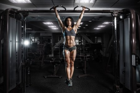 Photo for Sexy young fitness girl pulls up in the gym. Brunette fitness woman in gray sport wear with perfect fitness body in gym performing abdominal exercises on the horizontal bar - Royalty Free Image