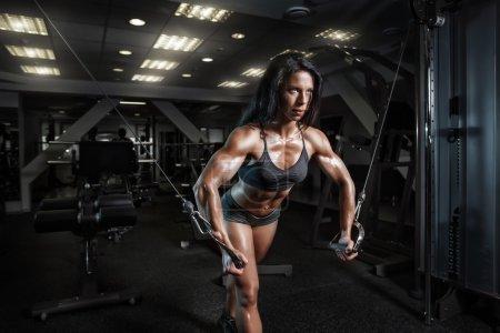 Photo pour Femme de fitness sexy en tenue de sport avec un corps de fitness parfait dans la salle de gym effectuant des exercices de poitrine - image libre de droit