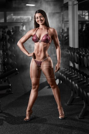 Sexy brunette bodybuilder woman in bikini. Posing and showing muscles in gym