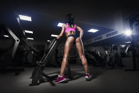 Fitness girl in gym in a sport wear. The back view of sexy young
