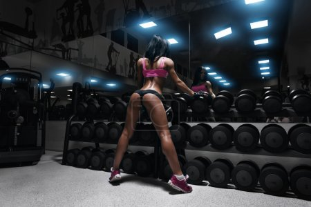 back view of sexy young brunette woman resting in the gym and le