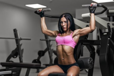 sexy young woman exercises in gym. Fitness woman in sport wear w
