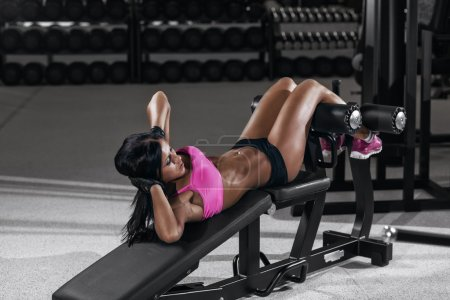 athletic brunette woman doing some crunches in a bench at the gy