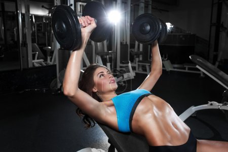 Photo for The fitness brunette girl perform chest training with dumbbells in the gym - Royalty Free Image