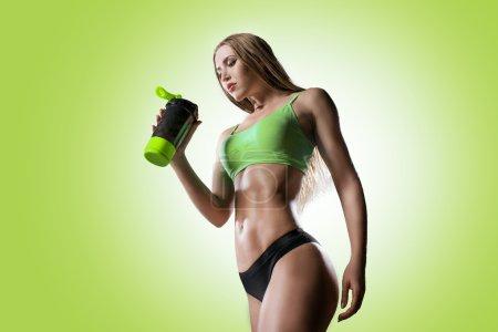 Photo pour La belle jeune femme athlétique avec une protéine cocktail dans un shaker se dresse sur un fond vert. Nutrition sportive. - image libre de droit