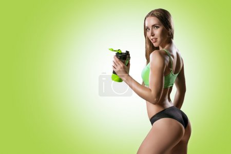 The athletic young beautiful woman with a protein ...