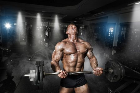 Photo for Athlete muscular bodybuilder in the gym training with bar - Royalty Free Image