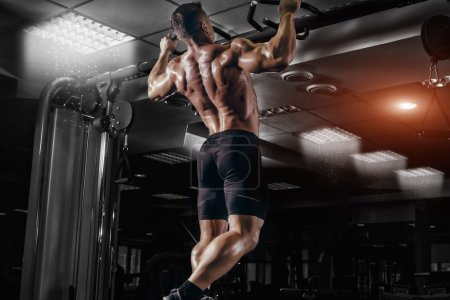 Photo for Muscle athlete man in gym making elevations. Bodybuilder training in gym - Royalty Free Image