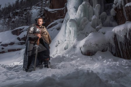 Photo for Medieval knight with sword in armor as style Game of Thrones in Winter Rock Landscapes - Royalty Free Image