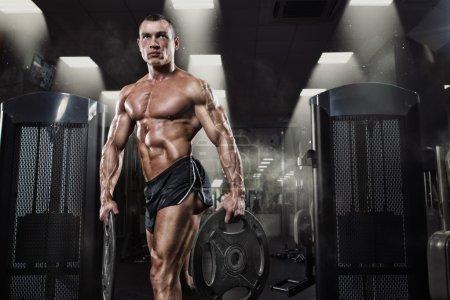 Professional bodybuilder with weight disk in gym. Weightlifter w