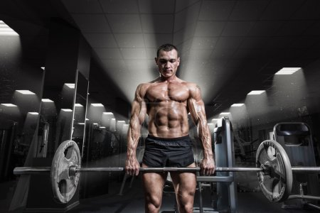 Muscular man workout with barbell at gym. Deadlift barbells work