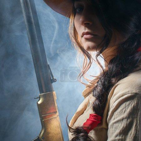 Photo pour Cowboy de la fille avec une arme à feu sur un fond gris - image libre de droit