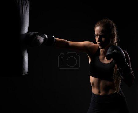 Photo pour Belle fille blonde en gants de boxe pousse le sac sur un fond noir - image libre de droit