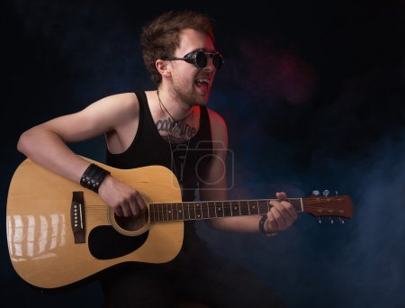 Photo for Handsome musician playing guitar on black background - Royalty Free Image