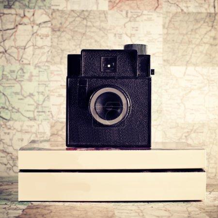 Photo pour Vieil appareil photo rétro avec livres sur fond de carte - image libre de droit