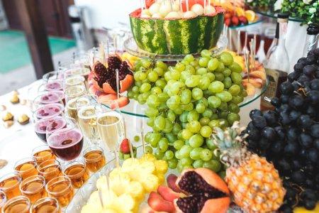 Photo pour Buffet riche, whisky, bourbon, champagne, vin et fruits . - image libre de droit
