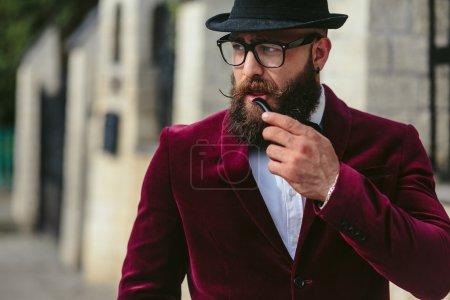 Foto de Un hombre rico con una barba fuma cigarrillo electrónico - Imagen libre de derechos