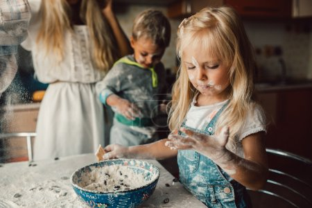 Photo for Kids is playing with flour in the kitchen - Royalty Free Image