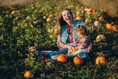 Photo for Mother and daughter on a field with pumpkins, Halloween eve - Royalty Free Image