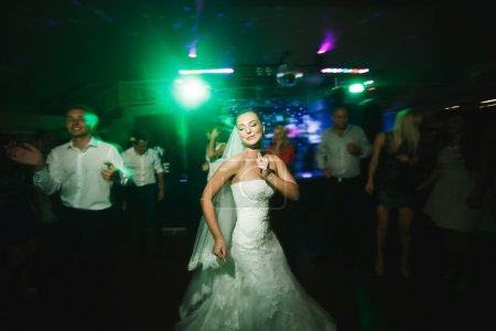 Photo pour Belle mariée et le marié danse parmi les gens sur la piste de danse - image libre de droit