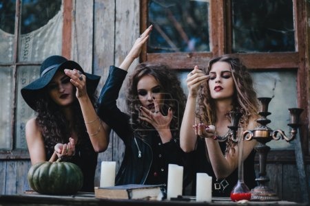 Three vintage witches perform magic ritual, throwi...